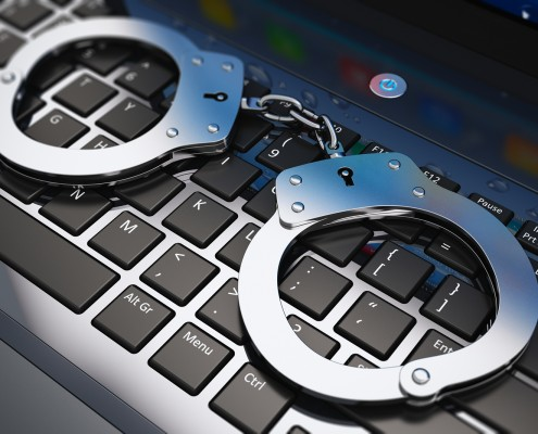 Cyber crime, online piracy and internet web hacking concept: macro view of metal handcuffs on laptop notebook keyboard with selective focus effect