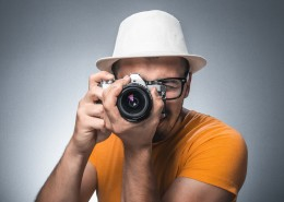 Man take photo of you - take a portrait. Guy photographs - take pictures. Photographer holding old retro vintage camera